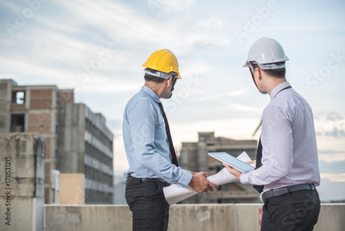 Smiling young architect or engineering builder in hard hat with tablet over grou Canvas Print