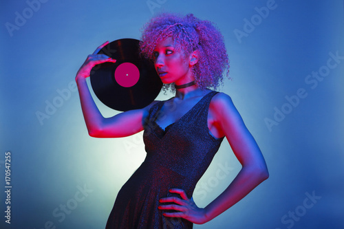 Photo millennial black woman with groovy hair holding an old eighties vinyl with retro