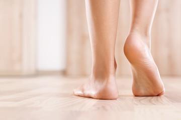 Płaskostopie. Zdrowa stopa dziecka. Stopy bosego dziecka na tle drewnianej podłogi