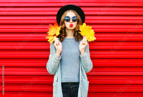 Fashion autumn portrait woman with yellow maple leaves on a red background - 170554062