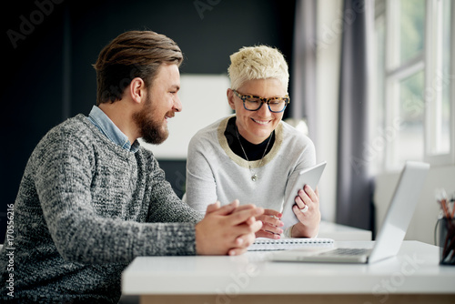 Fotografía  Businessman sitting and looking at tablet device while colleague showing him web