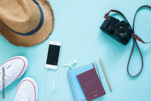 Fototapeta Flat lay of travel items with mobile device, passport and camera on pastel color background obraz na płótnie