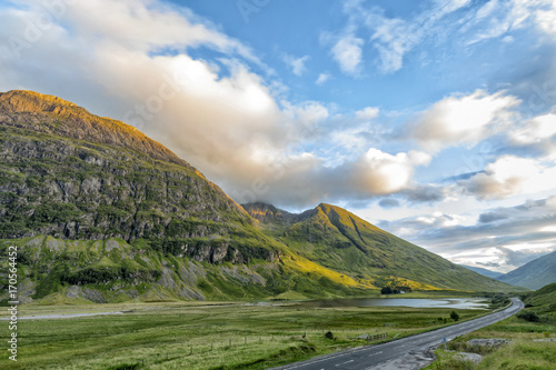 A82 highway runs through Glecoe with Loch Achtriochtan in the distance and mountains Aonach Dubh and An T-sron in Scotland Wallpaper Mural