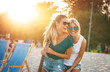 canvas print picture - Two young female friends hangout at the  beach ,singing and relaxing in beautiful summer sunset.They hug each other.Best friends.