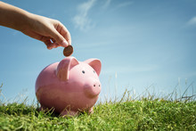 Child Hand Saving Money In Pig...