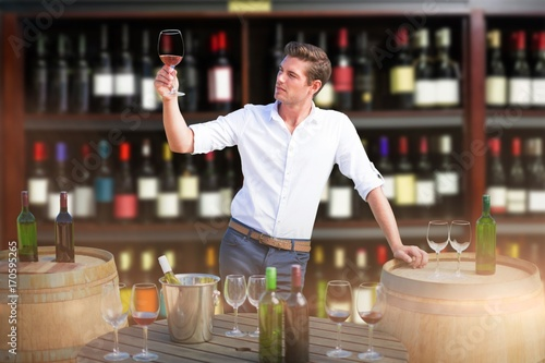 Photo  Composite image of young man holding red wine glass by barrels