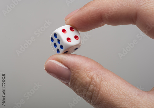 Female hand holding a dice isolated on white плакат