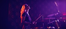 Young Female Drummer Performing In Illuminated Nightclub