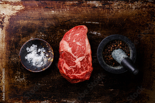 Raw fresh marbled meat Steak Rib eye Black Angus and seasoning on dark metal bac Wallpaper Mural