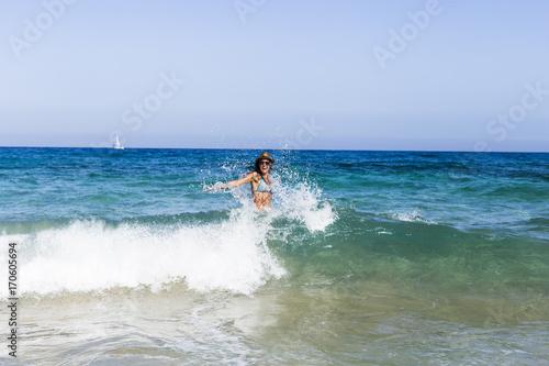 Fotografía  young beautiful woman having fun in the sea and crashing waves