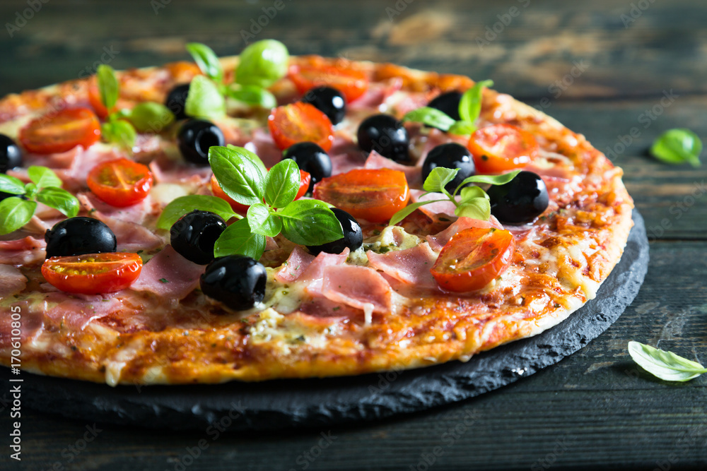 Pizza on a thin dough with olives and fresh basil