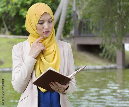 Zdjęcie XXL Piękna muzułmańska kobieta czyta książkę i myśleć w ogródzie