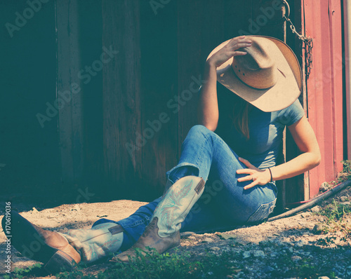 Cowgirl showing western fashion while sitting, wearing cowboy hat and boots.   Wall mural