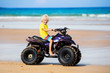 Child on quad bike at beach. All-terrain vehicle.