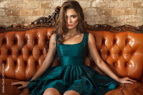 Luxury woman sitting at leater sofa in elegant green silk dress with evening make up.