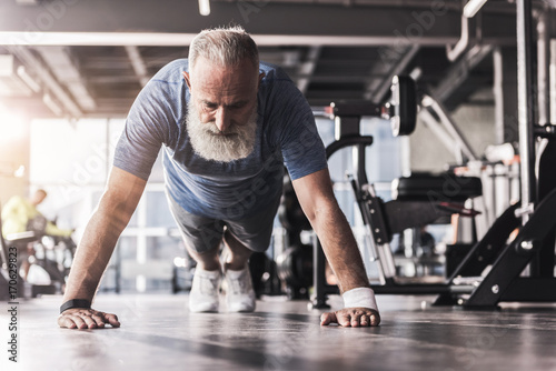 Fotografía  Bearded mature pensioner male is having workout in athletic club