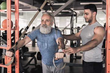 Confident senior male enjoying workout with trainer in athletic center