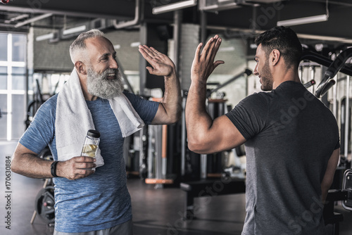 Poster Fitness Cheerful males are talking to each other in modern gym