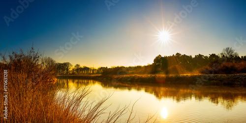 Plakat Piękny krajobraz z rzeką przy wschodem słońca