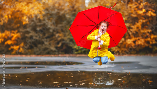 obraz PCV happy child girl with an umbrella and rubber boots in puddle on autumn walk