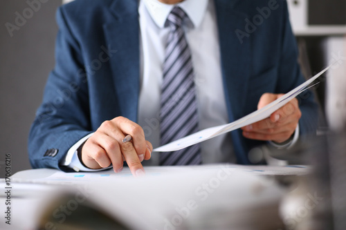 Foto  Male hands hold documents with financial statistics
