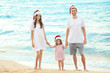 Young couple with cute girl on beach. Christmas concept