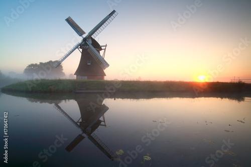 Fotobehang Molens charming windmill by lake at sunrise