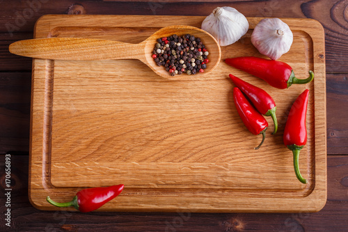 Poster Cuisine Kitchen background, cooking concept, free space for advertisement or text. Chopping board, garlic,chili peppers and spices in wooden spoon, ingredients for food and cuisine