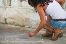 Women Makes A Heart In Chalk W...