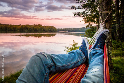 Wall Murals Camping Summer camping by the lake. Young man wearing jeans and sneakers relaxing in the hammock at sunset.