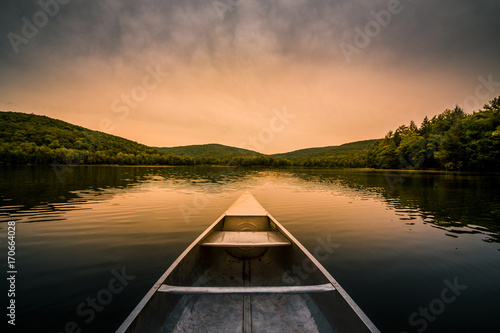 Photo Stands Lake Aluminum canoe on a mountain lake upstate New York. Camping. outdoors and adventure concept. Faded, vintage color post processed