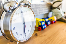 Closeup Of Modern Twin Bell Ring Analogy Clock On Wooden Table Desk Nightstand With Toy Trucks In Boy's Bedroom In Model House, Home Or Apartment