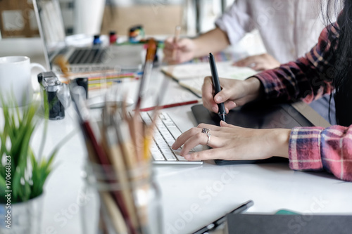 Photo Young female designer using graphics tablet while working with computer at studio or office
