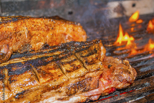 Türaufkleber Grill / Barbecue pork ribs marinated grilling on hot burning charcoal barbecue with some flames close-up