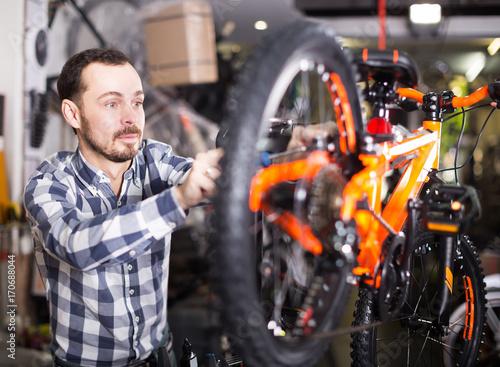 Foto op Plexiglas Fietsen Man going to mount bicycle wheel
