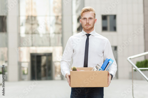 Valokuva  Unhappy bearded business man going out with cardboard, looking at camera and feeling looser