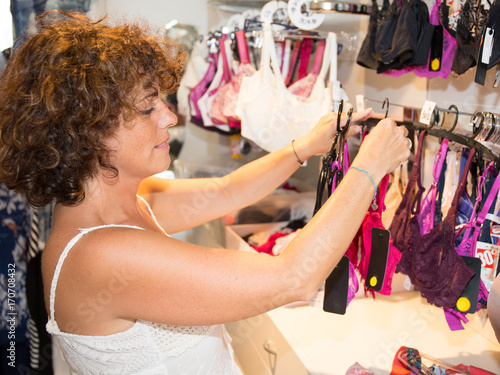 Woman shopping lingerie . Shopper looking and choosing clothing indoors in  store. Beautiful caucasian female 95bbbbd00