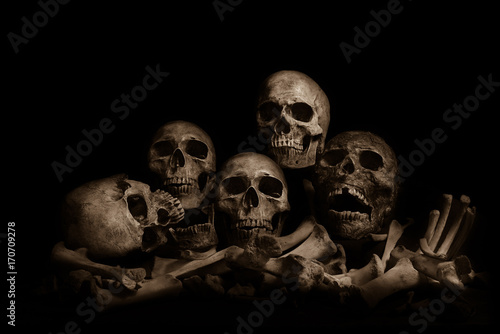 Photo Awesome pile of skull human and bone on wooden, black cloth background
