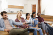 canvas print picture - Group Of Friends Sitting On Sofa Watching Television Together