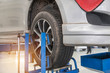 Car on lift to repair suspension in the garage to change motor oil and maintenance repair at service station