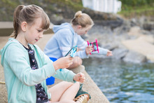 Two Girls Sitting On Harbour Wall Catching Crabs