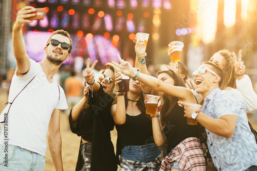 Friends drinking beer and taking selfie at music festival
