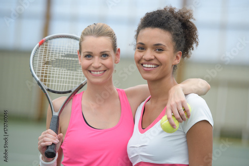 female tennis players playing doubles at the tennis court
