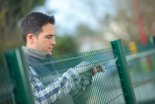 Worker Putting Up A Garden Fence