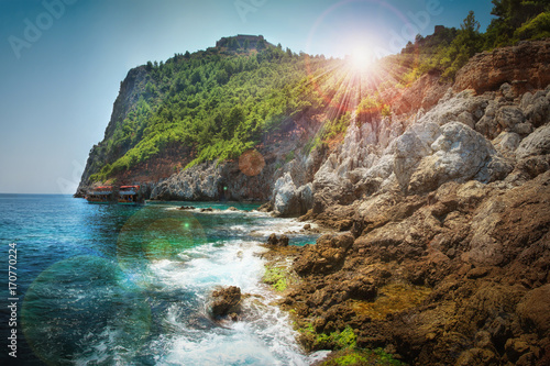 Poster Mer / Ocean Mountains and sea scenery with blue sky and bright sun rays over mount, Greece.
