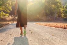 Feet Of A Woman Walking On A Dirt Road
