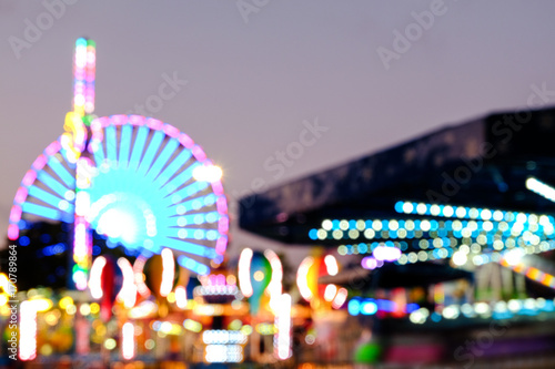 Foto auf Leinwand Vergnugungspark Abstract blur lights of ferris wheel and other attractions at night