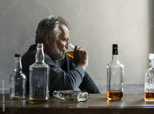 Fotografía  Elderly man sitting drinking whiskey alcoholic addiction bad habit