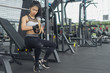 Fitness woman in training put fitness Gloves in gym