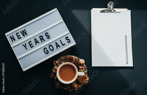 "Hot cocoa, Board with ""GOALS"" text, notebook, pencil on black background, top view, flat lay"